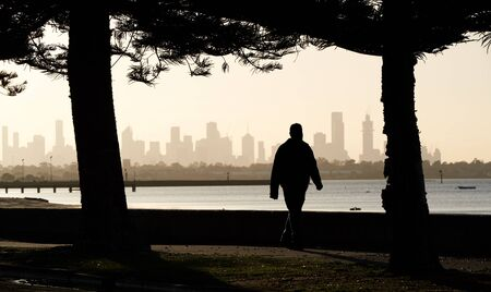 Early morning male walking silhouetted against the skyline of the city of Melbourne, Australia.