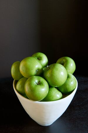 Green Granny Smith cooking apples in a white bowl against a brown background.