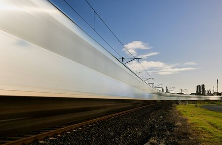 A blurred time lapse of a train travelling across the frame on a curve.