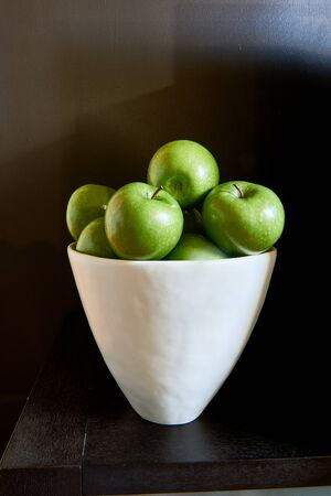 A white bowl full of green Granny Smith apples against a brown wall and table. 写真素材