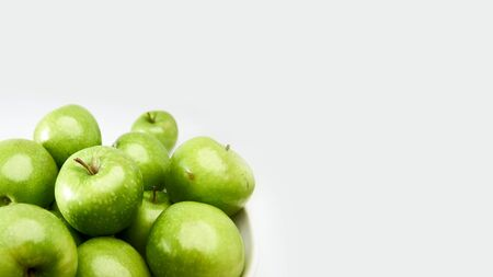 Green Granny Smith cooking apples in a white bowl from above against a light grey background with space for copy. 写真素材