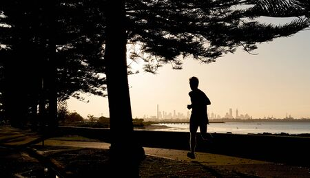 Early morning male jogger silhouetted against the skyline of the distance city of Melbourne, Australia.