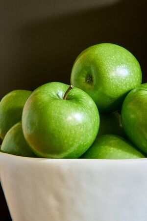 Green Granny Smith apples in a white bowl and dark brown background.