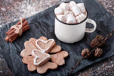 coffee mug with cookies and marshmallows, cinnamon sticks and fir cones Stock Photo