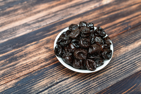 organic prunes in a bowl on a wooden background
