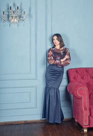the beautiful young woman the brunette to the utmost in a classical interior, blue plaster