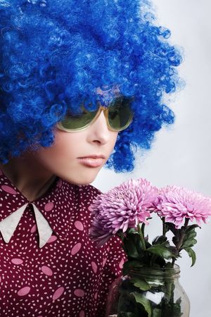 Young beauty clown  in dark blue wig with flowers photo