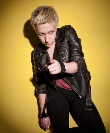 Strict woman in leather jacket on yellow background Stock Photo - 7131198