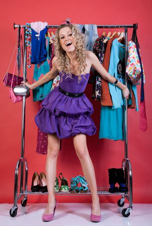 beautiful girl in fashion clothes in the dressing room on a red background photo
