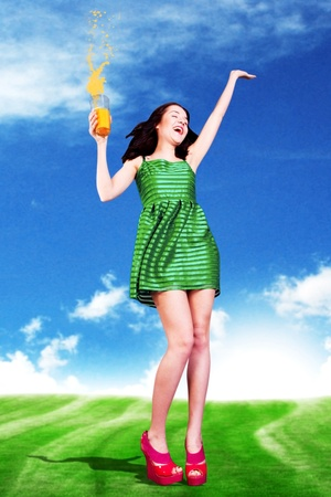 beauty young woman with orange juice, in green dress on sunny meadow photo