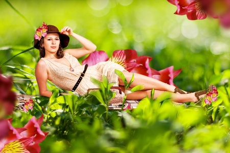 beauty young woman in green grass, with red flowers photo