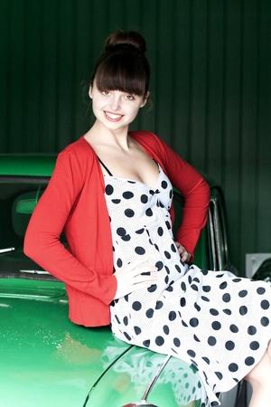 polka dot dress: beauty young woman on green car, vintage Stock Photo