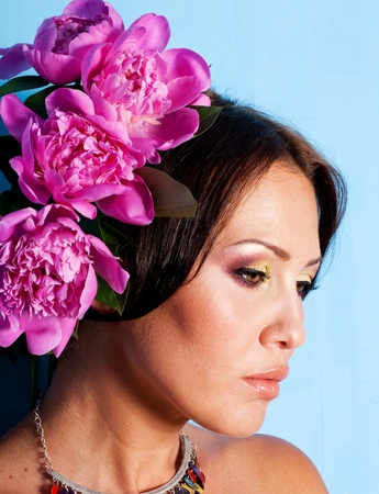 porrait of beautiful young woman with art make up and flowers photo