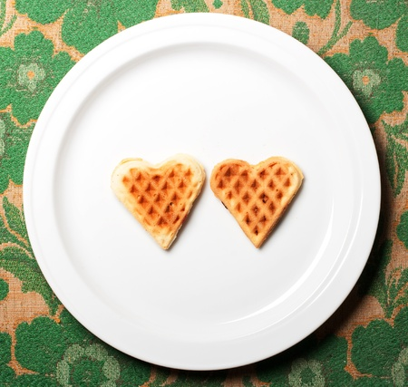 sweet wafer heart on dish, on retro background photo