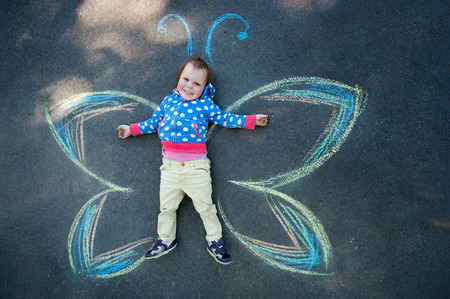 pavement: Little Girl smiling Butterfly drawing with chalk on the pavement