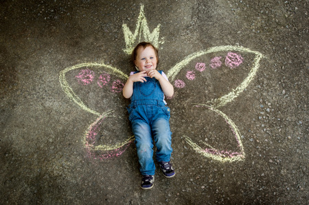 Little Fairy girl smiling drawing with chalk on the pavement photo