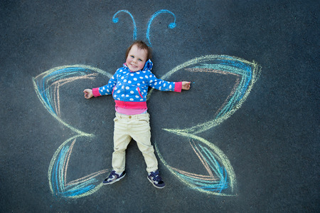 Little girl smiling Butterfly drawing with chalk on the pavement photo