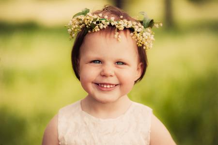 Little girl in wreath of flowers photo