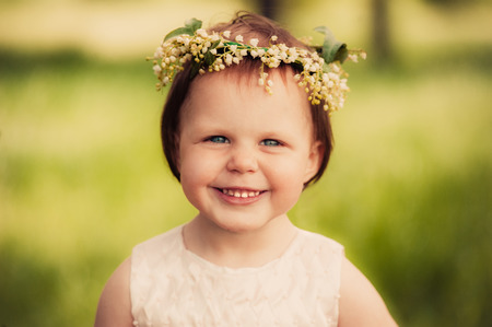 Little girl in wreath of flowers photo