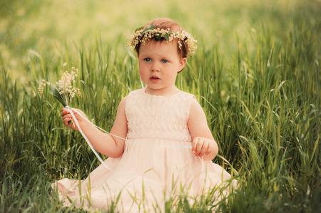 beautiful little girl in wreath of flowers photo