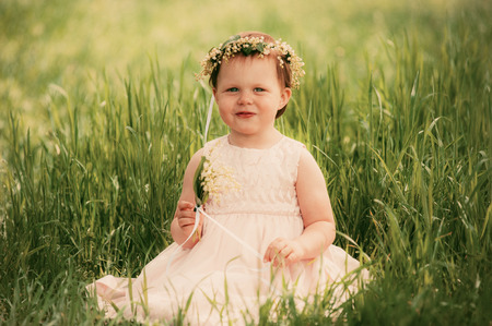 Little girl smiling child sitting on the grass photo