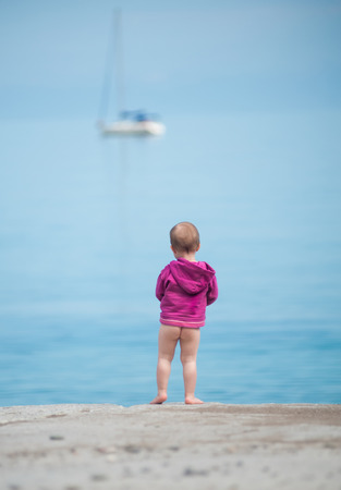 Little child looks at a ship at sea Stock Photo