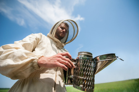 clouds making: beekeeper with smoke tool. making clouds.