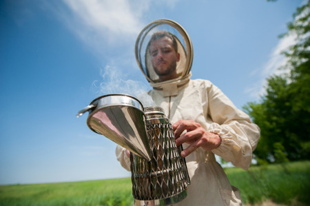 clouds making: beekeeper with smoke tool. making clouds