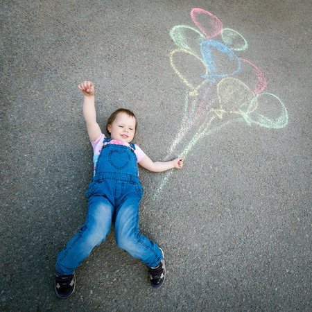 one girl only: Little Girl with balloons drawing with chalk on the pavement Stock Photo