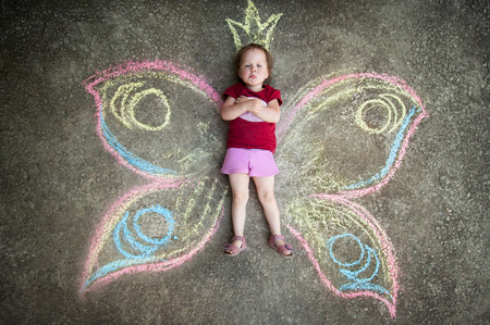 Little girl Butterfly CAPRICE. Drawing with chalk on the pavement Standard-Bild
