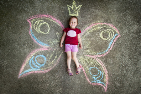Little girl Butterfly JOY. Drawing with chalk on the pavement photo