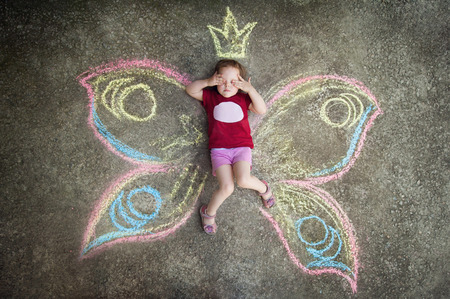 seek: Little girl Butterfly HIDE AND SEEK. Drawing with chalk on the pavement
