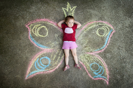 Little girl Butterfly SHYNESS. Drawing with chalk on the pavement photo