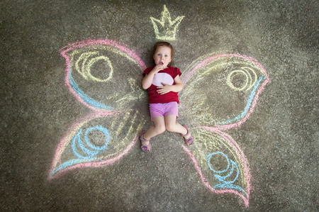 wonders: Little girl Butterfly SURPRISE. Drawing with chalk on the pavement