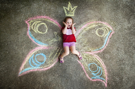 one girl only: Little girl Butterfly SURPRISE. Drawing with chalk on the pavement