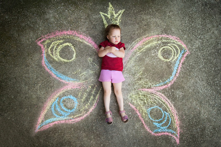 Little girl Butterfly RESENTMENT. Drawing with chalk on the pavement photo