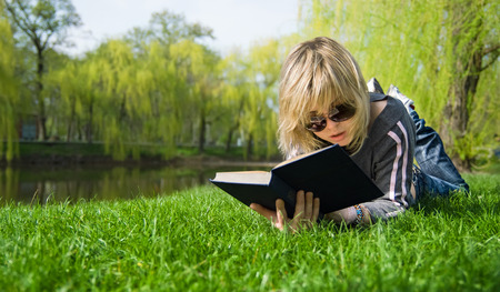 only one girl: girl reading a book lying on the grass