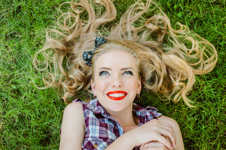 capelli biondi: Happy Girl blonde smiling lying on the grass