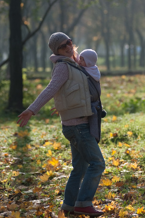 rejoice: Mom and baby in a sling rejoice falling autumn leaves Stock Photo