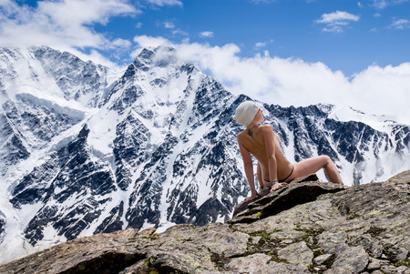 Attractive girl topless on the background of snowy mountain range