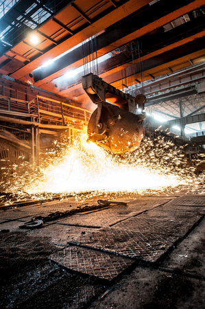smelting plant: from ladle pours red-hot steel Stock Photo