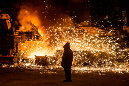 burningout: Steelworker near a blast furnace with sparks
