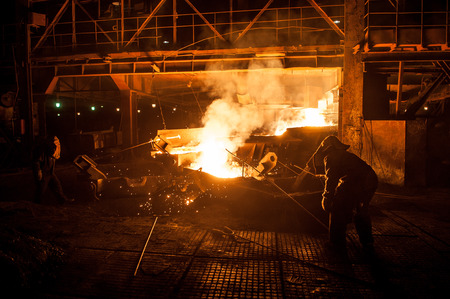 Steelworkers when pouring liquid titanium slag from arc furnace