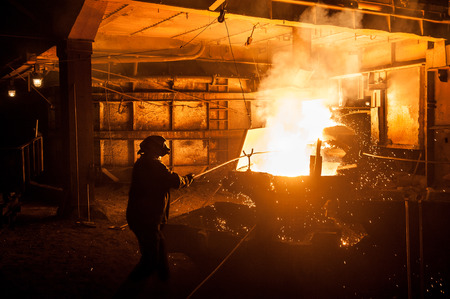 slag: Steelworker when pouring liquid titanium slag from arc furnace