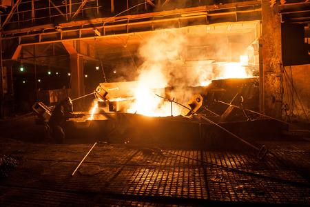 steelmaker: Steelworker when pouring liquid titanium slag from arc furnace