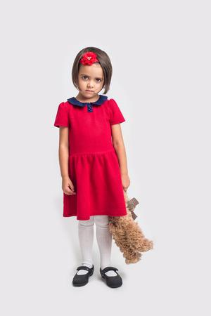 ojos tristes: Descontento niña hermosa en un vestido rojo con un oso de juguete