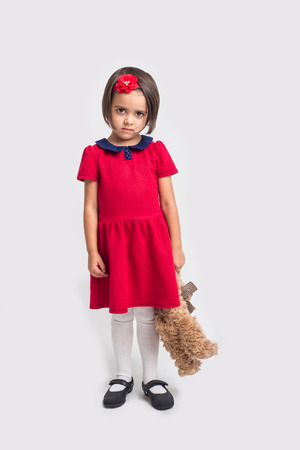 girl holding flower: Unhappy beautiful little girl in a red dress with a toy bear