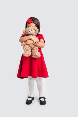 bebes ni�as: Ni�a en un vestido rojo con un oso de juguete Foto de archivo