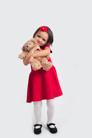 Beautiful smiling little girl in a red dress with a toy bear