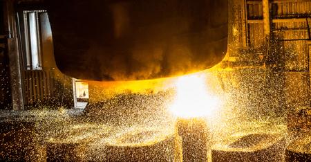 steelmaker: Steelworker pours liquid metal into molds from tank